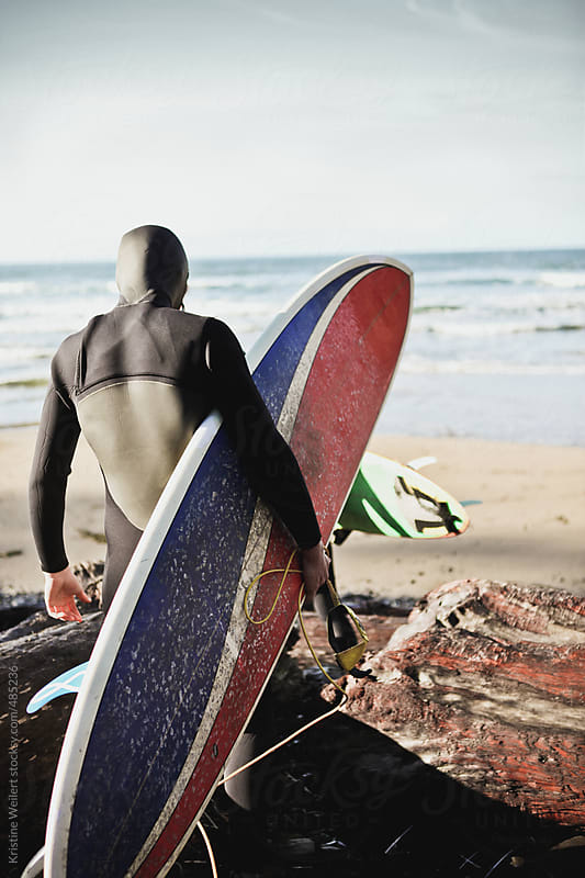 Man in wet suit holding surfboard by Kristine Weilert for Stocksy United