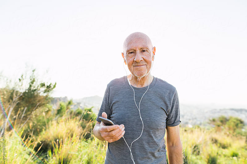 Portrait of a senior man listening music with his phone after workout.  by BONNINSTUDIO for Stocksy United