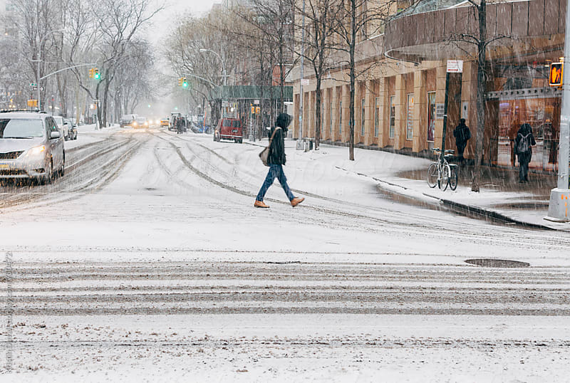 Pedestrian crossing street during snowstorm. New York City. by Kristin Duvall for Stocksy United