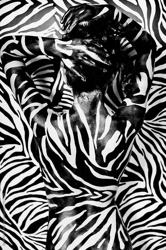 Woman with black and white stripes in front of a black and white background by Beatrix Boros for Stocksy United