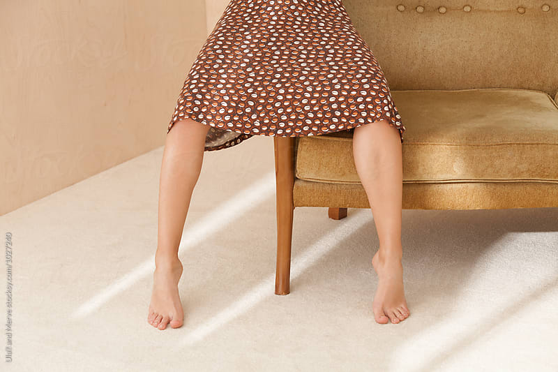 legs of lady sitting on retro couch by Ulaş and Merve for Stocksy United