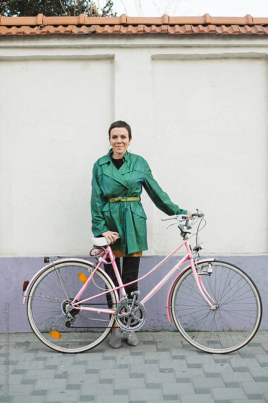 Woman with a Pink Bicycle Standing in front of the Purple Wall by Katarina Radovic for Stocksy United
