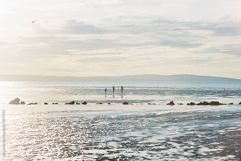three kids on the beach at low tide by Léa Jones for Stocksy United
