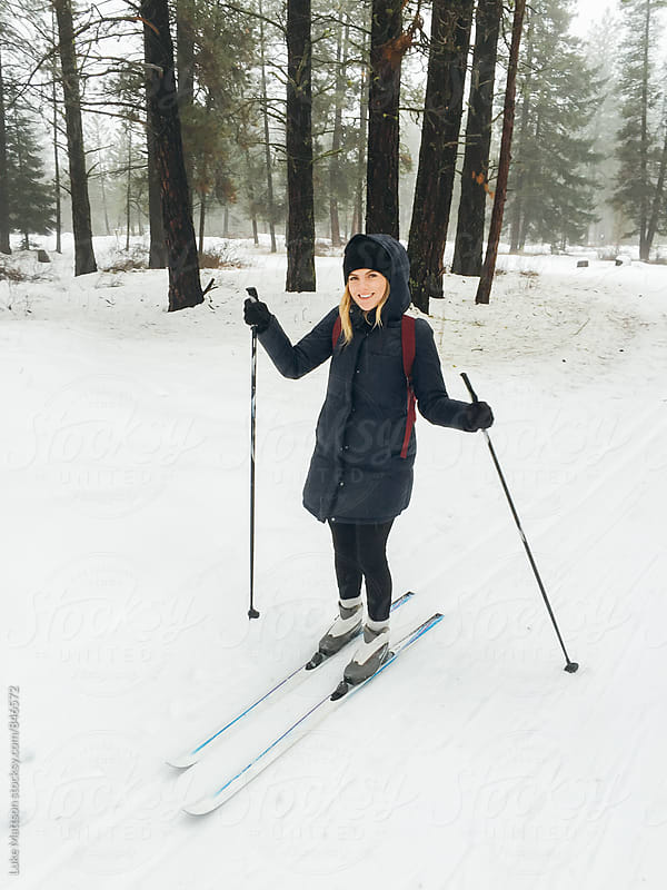 Smiling Young Blonde Woman Cross Country Skiing Along Snowy Trail Through Winter Forest by Luke Mattson for Stocksy United