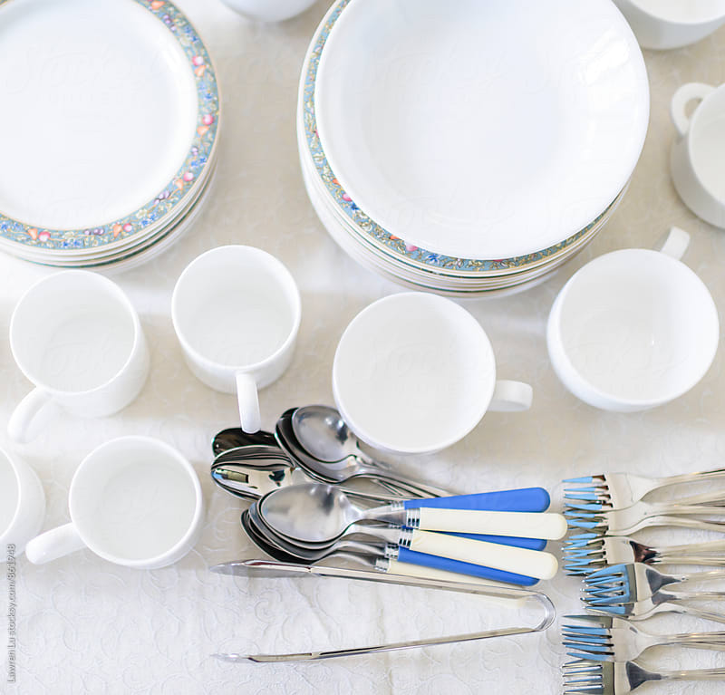 Clean white tableware of plates, bowls, cups, spoons and forks by Lawren Lu for Stocksy United