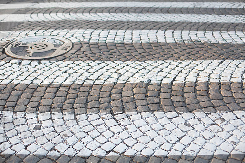 Zebra crossing on paving stone. by Nabi Tang for Stocksy United