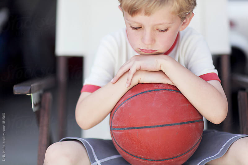 a sad little boy with a  basketball by Kelly Knox for Stocksy United