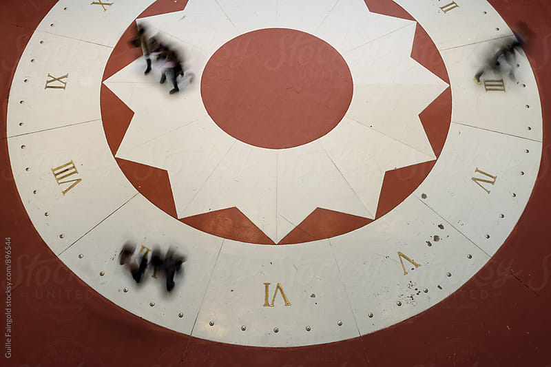 people walking over sun clock. view from above by Guille Faingold for Stocksy United