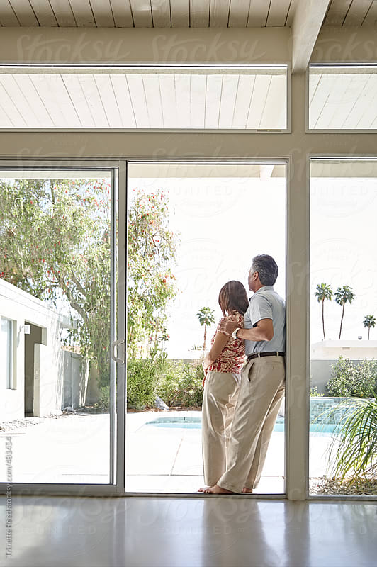 Mature couple looking out window in modern design home by Trinette Reed for Stocksy United