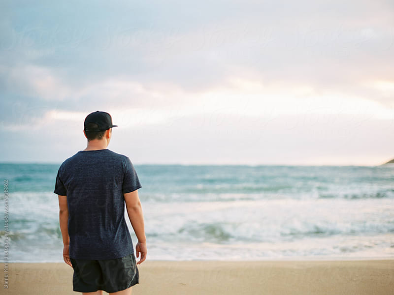 Young man looking out at ocean by Daniel Kim Photography for Stocksy United