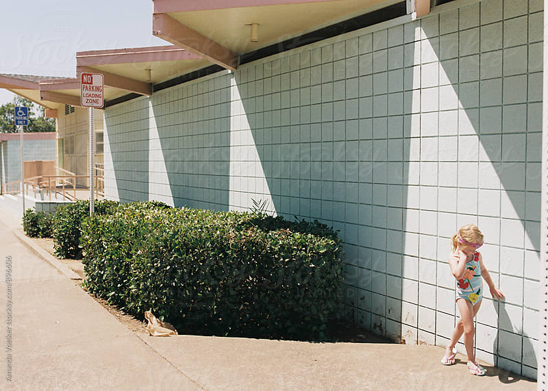 Little Girl Stands Outside Of Retro Swim Center by Amanda Voelker for Stocksy United