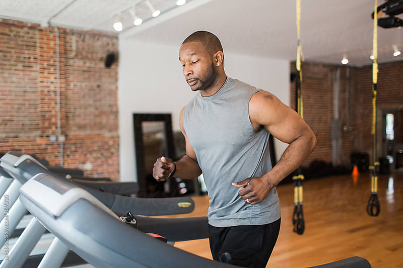 Muscular African-American man running on a treadmill by Jakob for Stocksy United