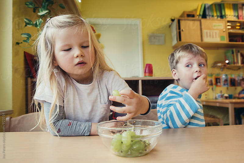 People: Two children eating lunch in Kindergarden by Ina Peters for Stocksy United