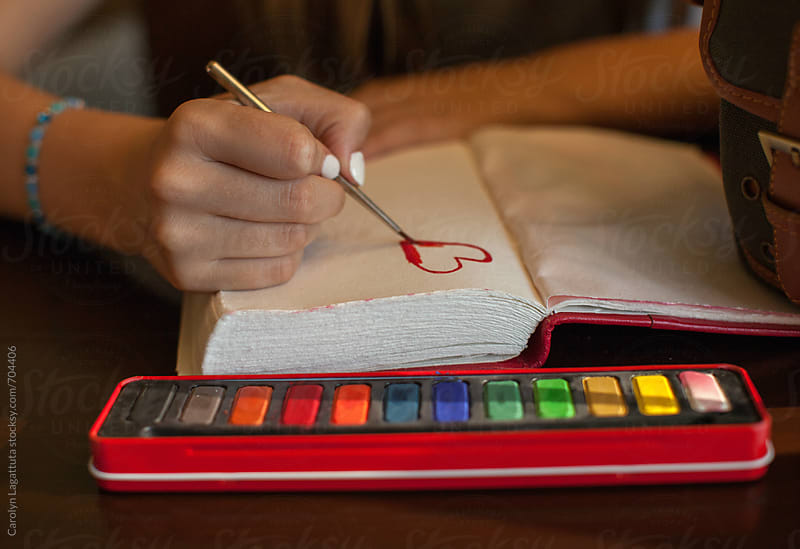 Teen girl painting a heart in her journal by Carolyn Lagattuta for Stocksy United