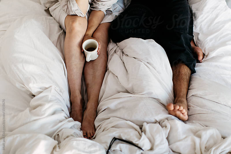 Drinking coffee in bed by Matt and Tish for Stocksy United