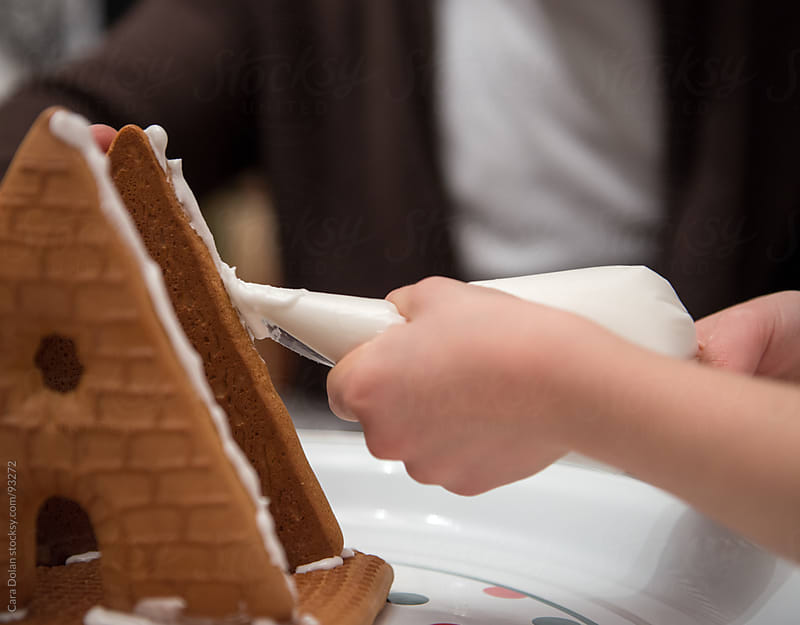 A child's hands squeeze out frosting from a bag onto gingerbread house parts by Cara Dolan for Stocksy United