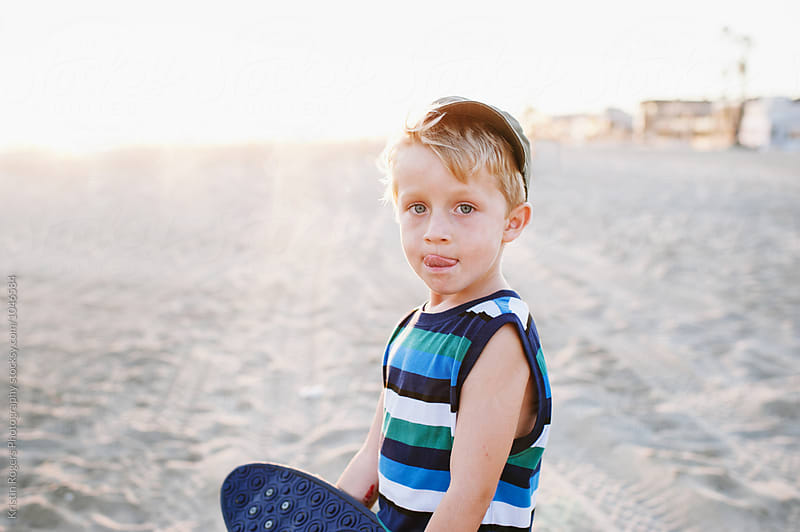 Cute young boy holding skateboard on beach at golden hour by Kristin Rogers Photography for Stocksy United