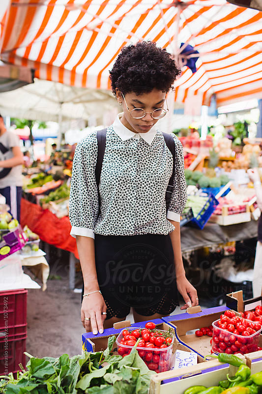 Young woman shopping at the local vegetable market by michela ravasio for Stocksy United