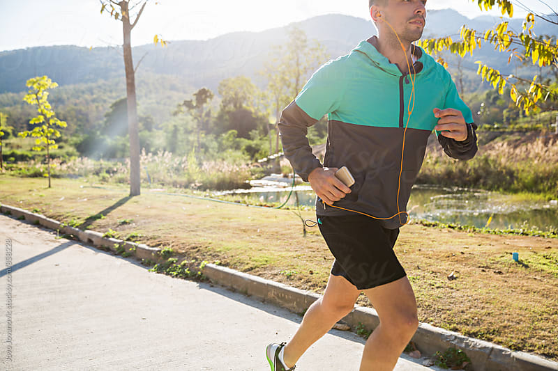 Fit young man running in the nature and listening to music on his smartphone  by Jovo Jovanovic for Stocksy United