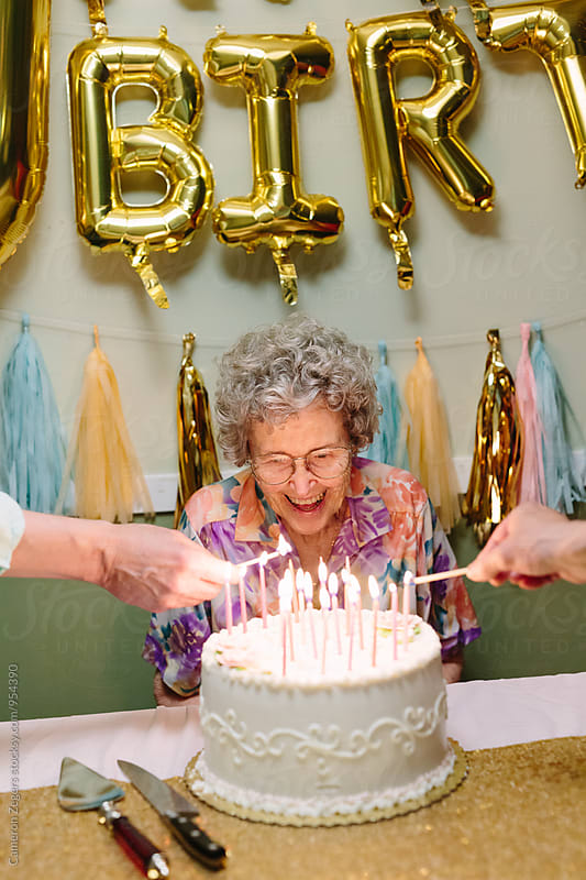 elderly woman celebrating birthday by Cameron Zegers for Stocksy United