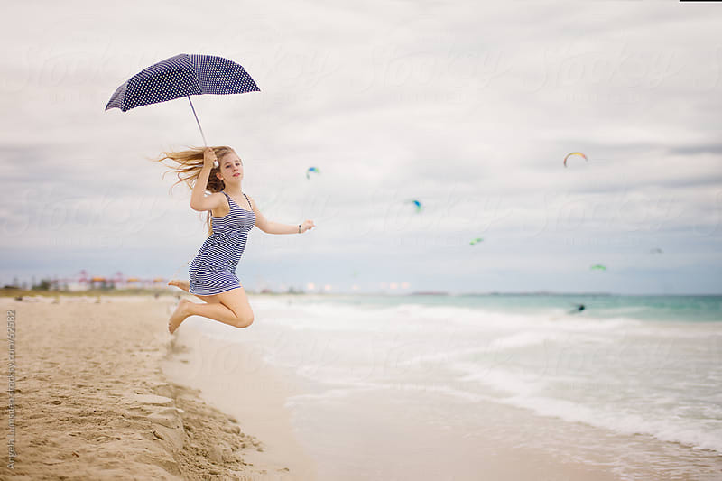 Girl jumping with an umbrella at the beach by Angela Lumsden for Stocksy United