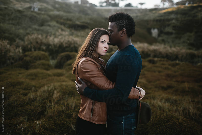 attractive couple hugs in field of dark green grass by Nicole Mason for Stocksy United