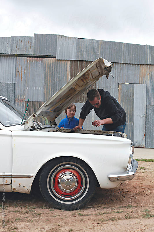 Young boy helps his Dad fix their vintage retro car by Natalie JEFFCOTT for Stocksy United