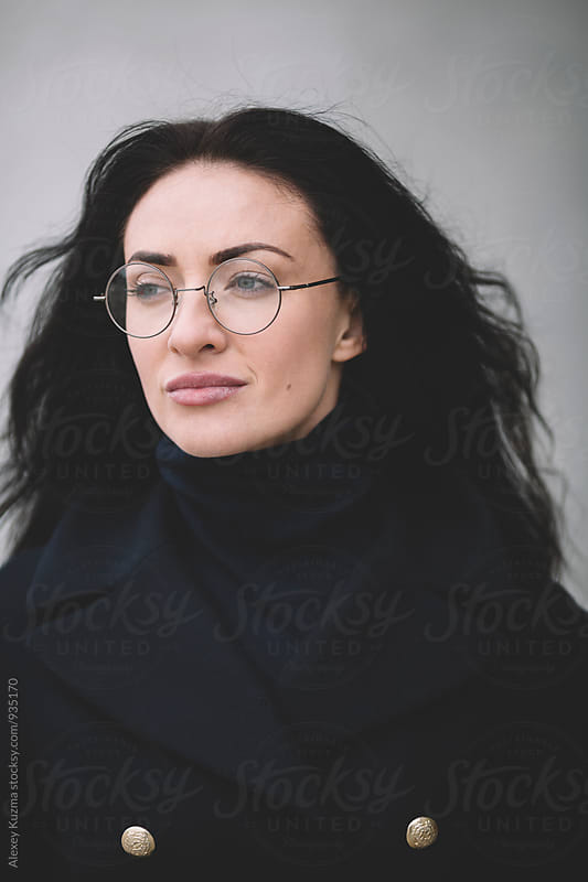 young woman with round glasses  by Alexey Kuzma for Stocksy United