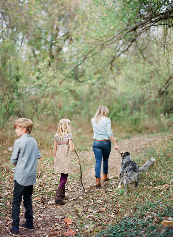 Mother and her two kids and dog hiking in the woods by Marta Locklear for Stocksy United