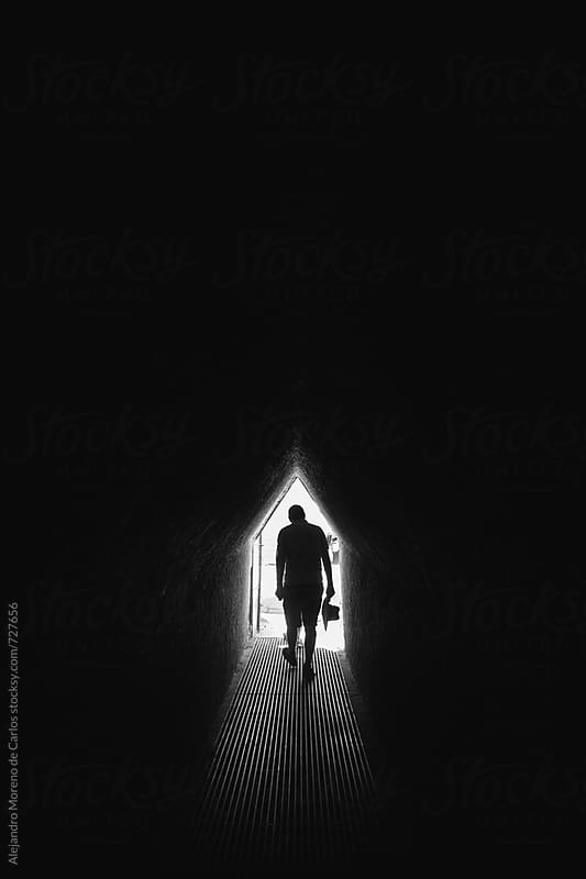 Silhouette of a man walking through an underground tunnel in black and white by Alejandro Moreno de Carlos for Stocksy United