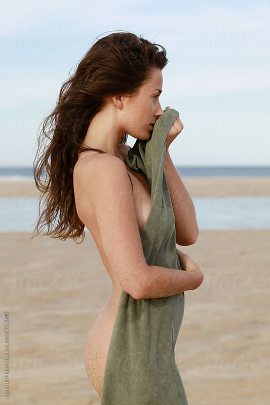 young woman on the beach, holding towel by Rene de Haan for Stocksy United