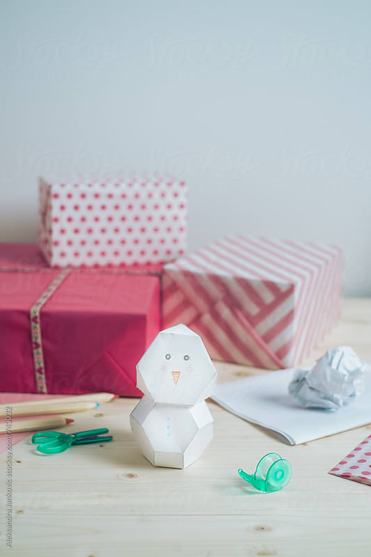 Paper Snowman on the Desk in Front of Pink Christmas Presents by Aleksandra Jankovic for Stocksy United
