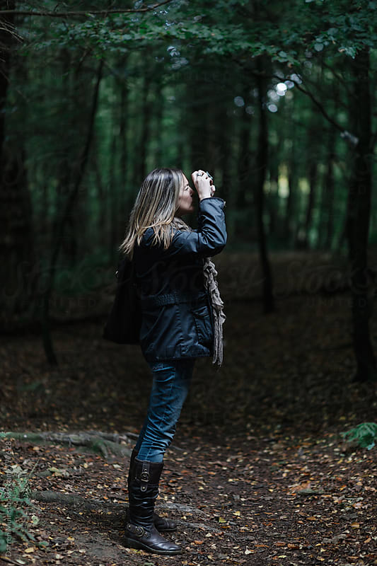 Woman taking photographs in a forest.  by Darren Muir for Stocksy United