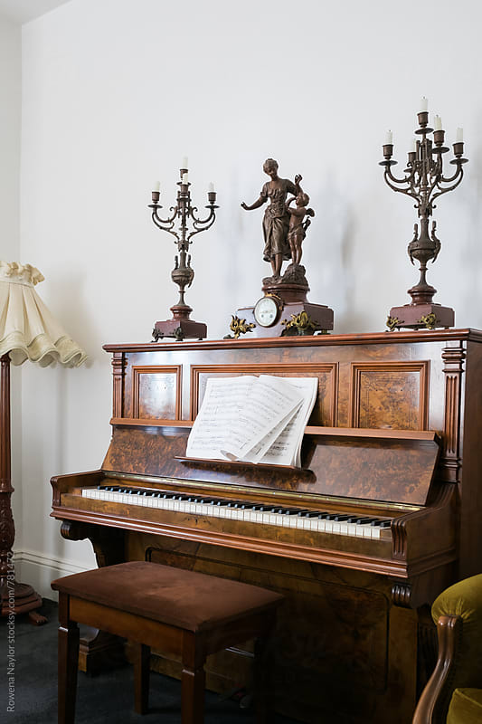 Old walnut piano with sheet music by Rowena Naylor for Stocksy United