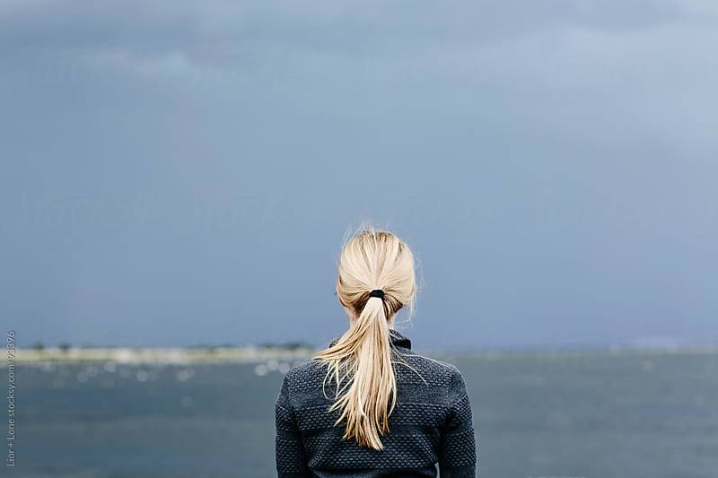 Blond woman staring at the sea by Lior + Lone for Stocksy United