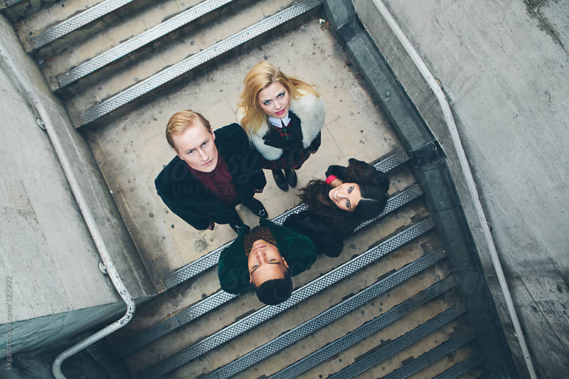 Group of four people on a stone staircase by kkgas for Stocksy United