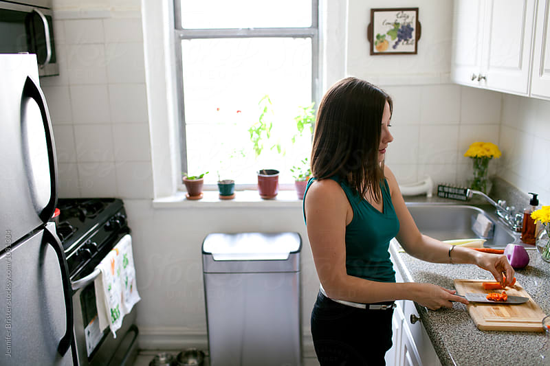 Woman cooking in small kitchen by Jen Brister for Stocksy United