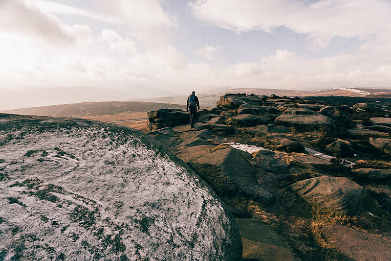 Male with backpack walking in the snow on Stanage Edge. Derbyshire, UK. by Liam Grant for Stocksy United