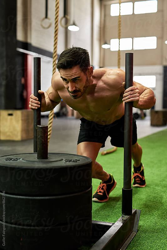 Man pushing weighted sled in a gym by Guille Faingold for Stocksy United