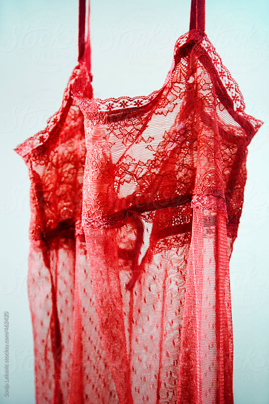 red lace lingerie on blue background by Sonja Lekovic for Stocksy United