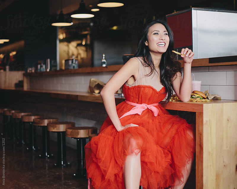 Girl eating a burger in a red dress by Ania Boniecka for Stocksy United