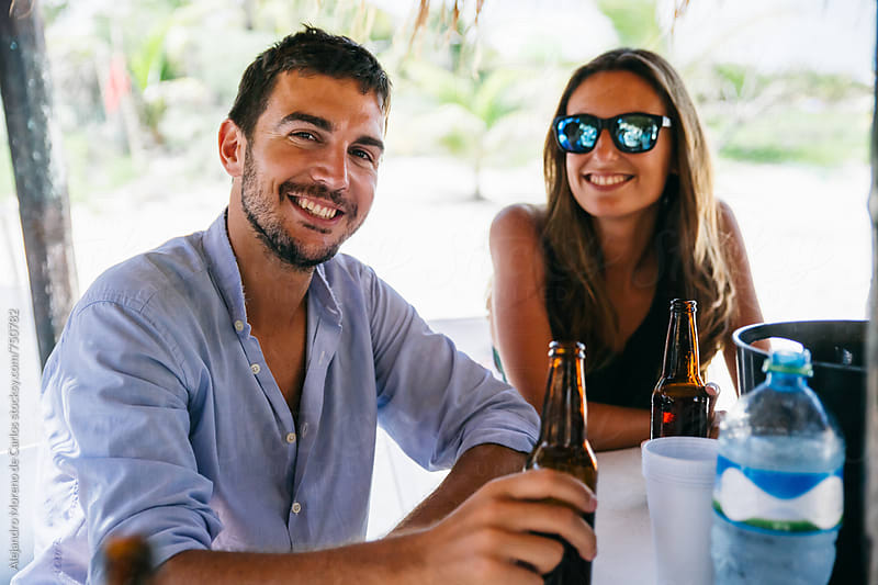 Young happy couple enjoying some drinks in a beach bar by Alejandro Moreno de Carlos for Stocksy United
