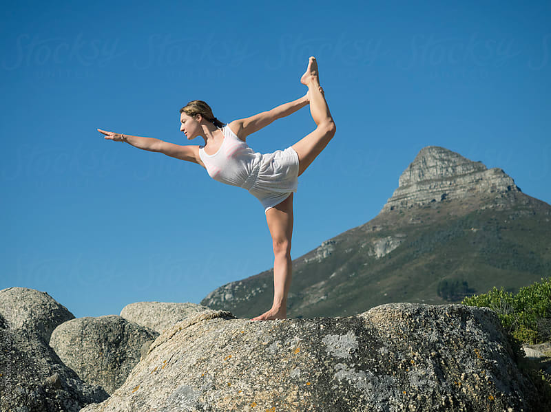 Young woman doing Yoga on the rocks by the sea by DV8OR for Stocksy United