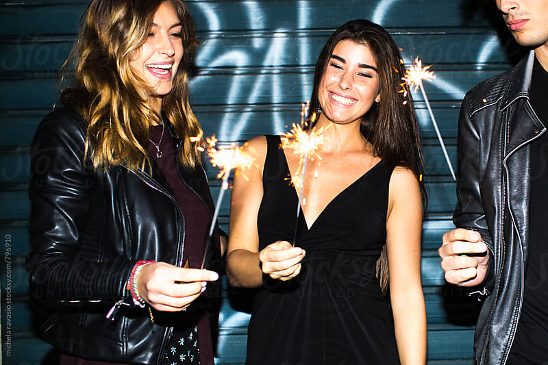 Friends celebrating together with sparkles by michela ravasio for Stocksy United