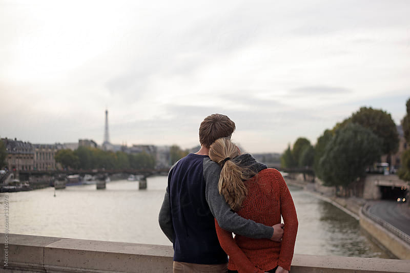 Young couple on a bridge in Paris by Marcel for Stocksy United