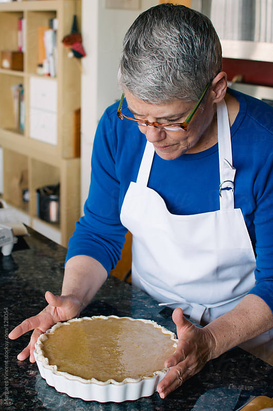 woman prepares pumpkin pie by Margaret Vincent for Stocksy United