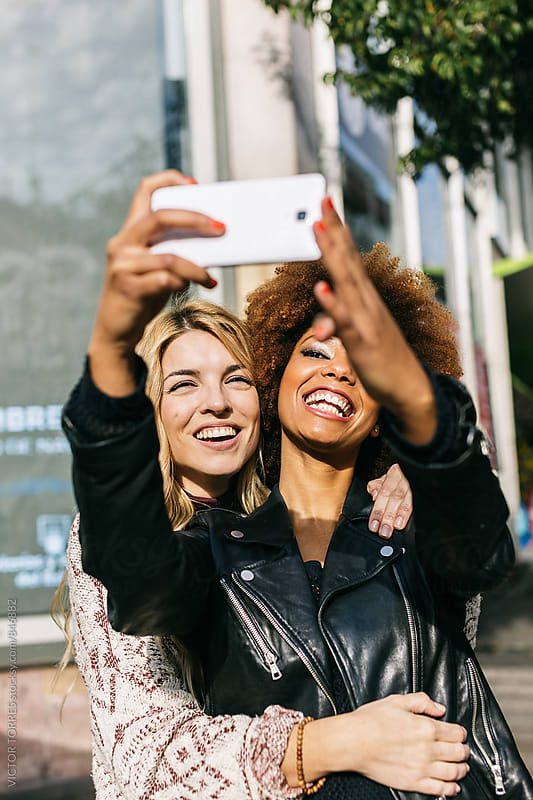 Young Couple of Women Taking a Selfie in the Street by Victor Torres for Stocksy United