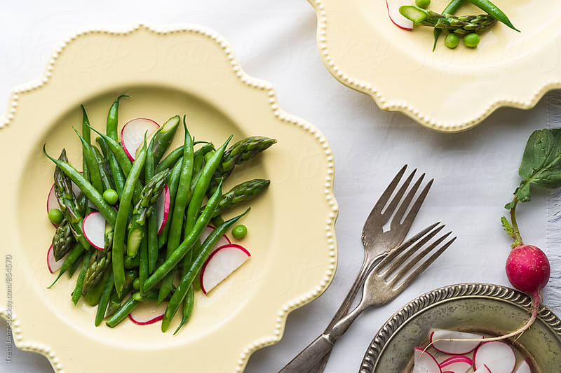 Fresh vegetarian dish made of asparagus, radish and green peas by Trent Lanz for Stocksy United