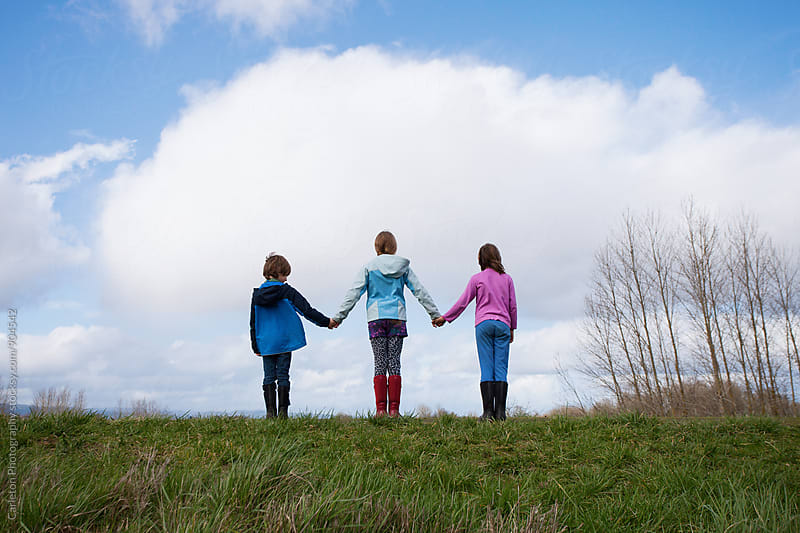 Three children holding hands at the top of a grassy embankment by Carleton Photography for Stocksy United