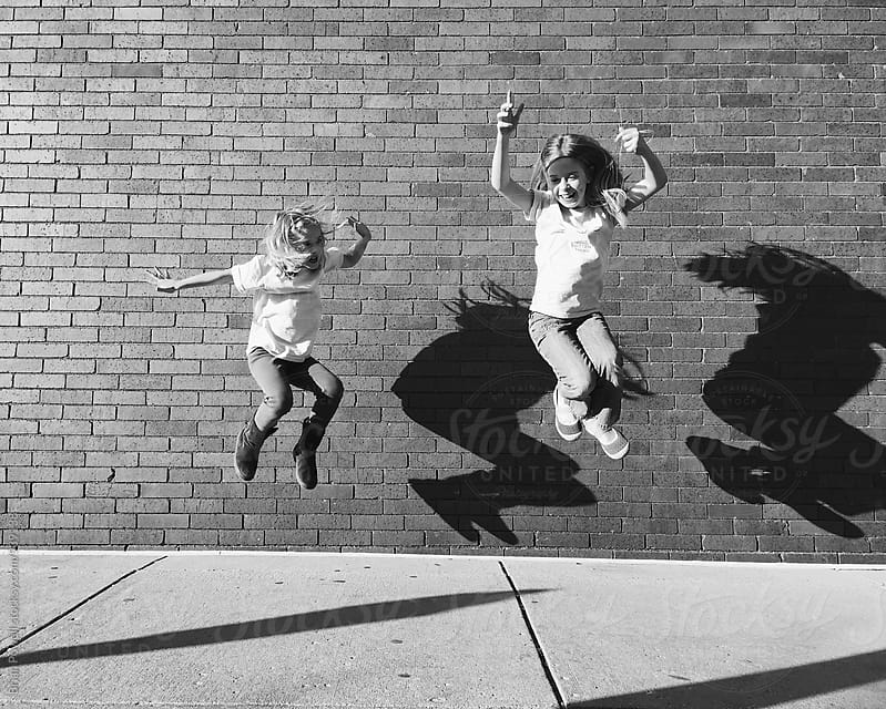 two sisters jump for joy by Brian Powell for Stocksy United